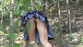 a girl in a short dress and without panties climbs up the mountain.